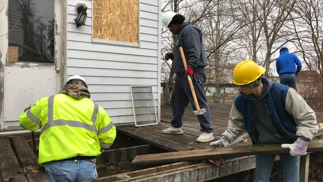Vanguard Career Center students Carter Flanagan, left, Tariq Williamson, middle, and Robert Ansted, right, work to remove a rotted deck at 323 Tiffin St.