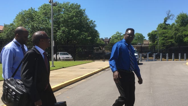 Plaintiff George L. Wade Jr., right, leaves William M. Colmer Federal Courthouse with his attorneys after his case against a Hattiesburg police officer was settled soon after trial began Tuesday, April 10, 2018.
