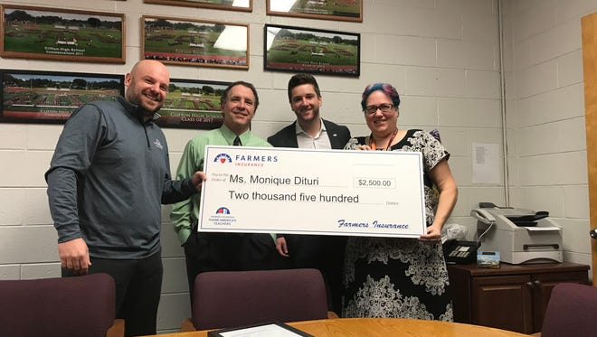 Timothy Pristas, Darren Smith and Vincent Fusco and the Farmers Insurance team present the grant check to Clifton teacher Monique Dituri.
