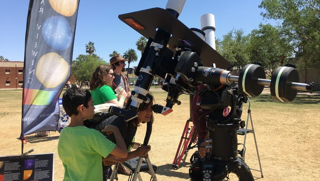 Darius Collins, 10, and his mother, Pardis Collins, look at the sun through filters in a telescope provided by Focus Astronomy Outreach at March For Science Phoenix on April 14, 2018.