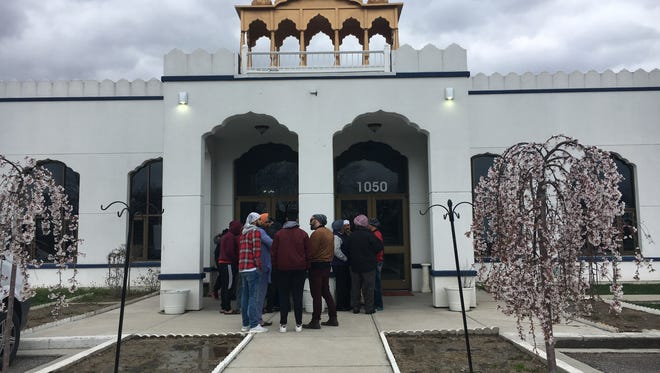 Members of the Gurdwara Sikh Temple stand outside the Greenwood building Sunday evening. A large brawl outside a temple left multiple people hurt.