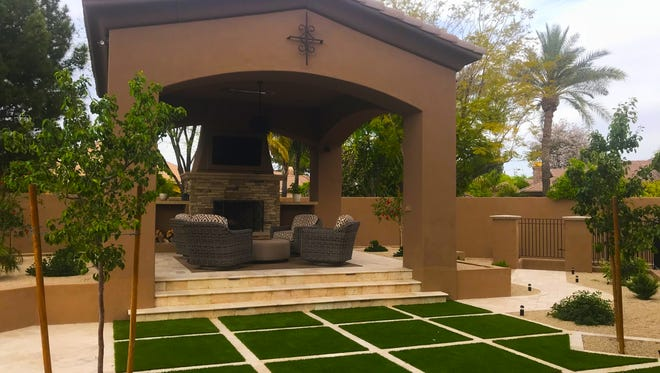 The homeowners chose this element of synthetic grass to add a pop of color in front of this gazebo.