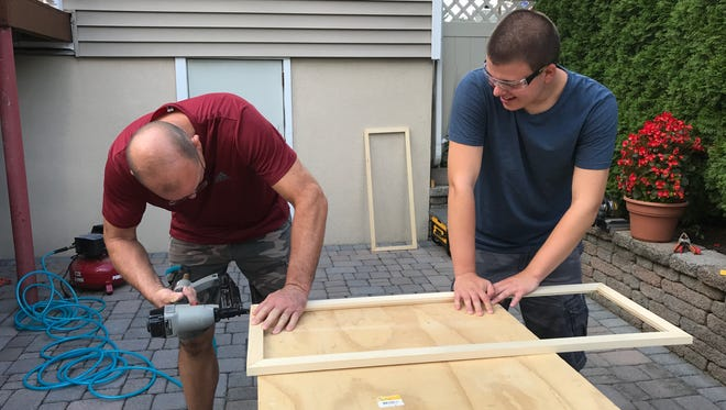 Luke Mulroony, right, and his father, Tim, make a frame for putting a puzzle inside. Luke, 17, of Totowa, has autism and makes puzzles for friends, family members and other people to buy.