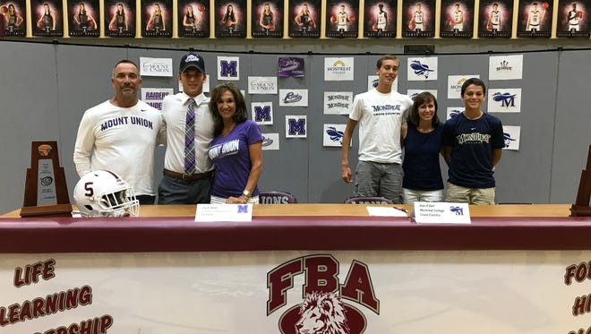 Zach West (left center) and Dan O'Dell (right) pose with their families after signing their national letters of intent at a signing ceremony in First Baptist Academy's gym on Wednesday, April 18, 2018.