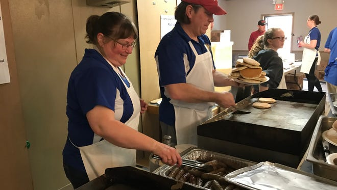 Pat Gerber, left, and Tom Bowlus stack sausages and pancakes that are ready to be served during the Kiwanis Pancake Festival at Anjulina's.