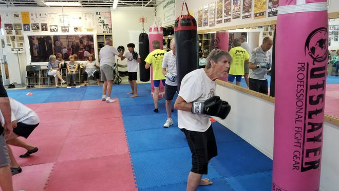 Members hit the bag during a Rock Steady Boxing class at Unlimited Kickboxing in Merritt Island