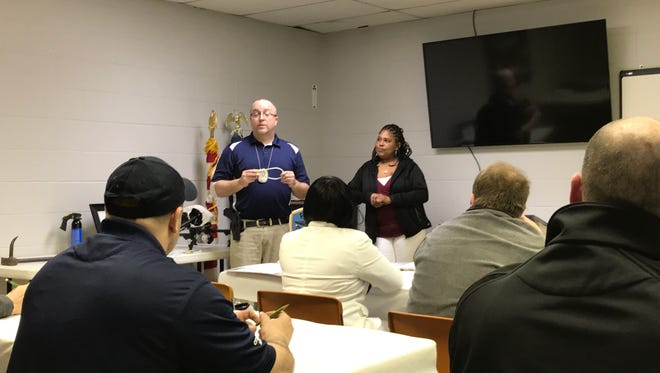 Fremont Police Detective Jason Kiddey displays a gun lock with guest speaker Jackie Richardson, who discussed gun safety at Thursday's Citizens Police Academy.