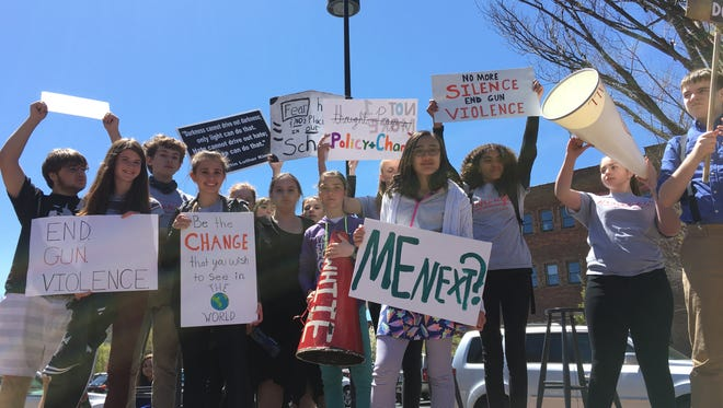 Students participating in the national walkout day to protest gun violence gather on Johnson Street in Staunton, Friday April 20, 2018.