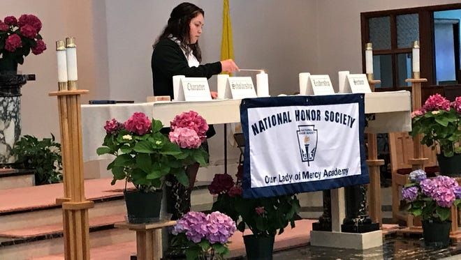 Allyson McCormick, a senior, assists with the candle lighting during Our Lady of Mercy Academy's National Honor Society induction ceremony.