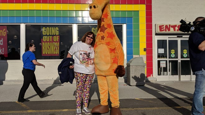 Sarah Roth stands with Toys R Us mascot Geoffrey the Giraffe at a final gathering of employees who worked at the Roseville location of the closing toy store.