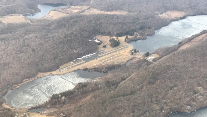 An aerial photograph over Aeroflex-Andover Airport in Andover, New Jersey. The 2,000 foot runway is flanked by two lakes on each side. Lake Aeroflex is pictured right, and Gardners Pond is to the left.
