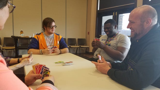 Monroe Township High School special needs students have a lively discussion over a game of Uno with educators and volunteers at the Monroe Township Senior Center on April 16.