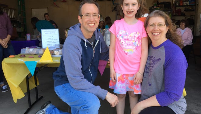 Kylie Myers-Schleif and her parents, Mike and Ruthie, at Sunday's Kickin' Cancer Lemonade Stand.