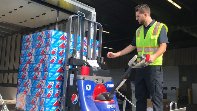 Tanner Reynolds, an employee with Pepsi Co. at the company's satellite warehouse in Hurricane, loads a truck using a new pallet jack.