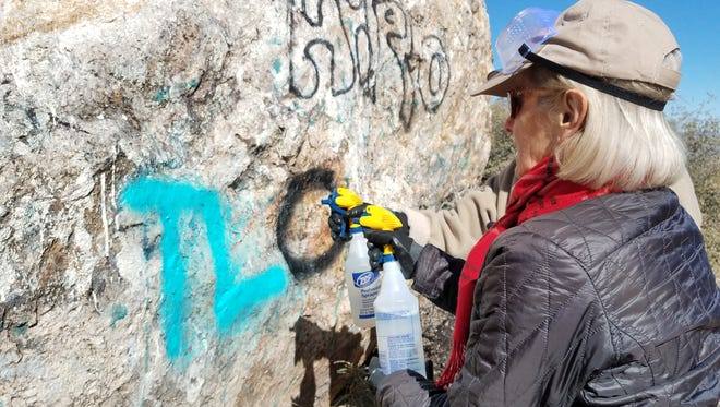 A volunteer removes graffiti at the Gold Butte National Monument