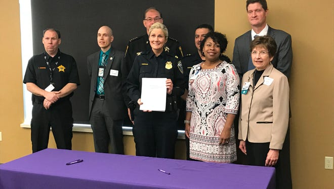 Milwaukee Police Capt. Aimee Obregon holds up the signed protocol for how police, prosecutors and other partners should respond to sexual assault victims.