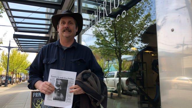 Brian McNett holds up a copy of a 1991 newspaper story about Avram Davidson.