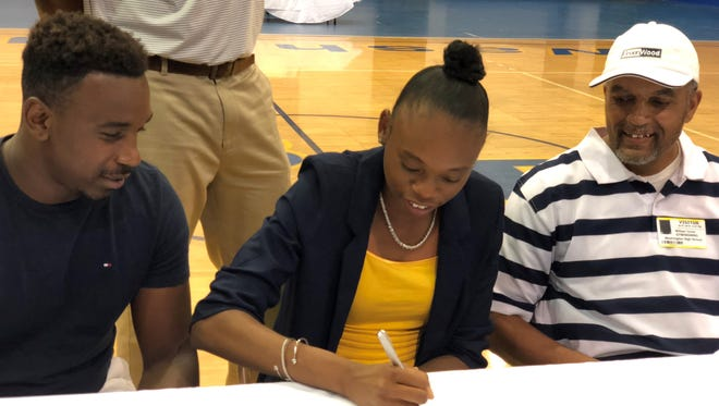 Washington High senior Tytavia Hardy signs with Mississippi College for track & field, joined by (right) father William Turner and brother Taliris Hardy.