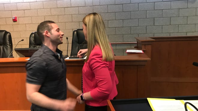 Sobriety Court graduate Matthew Abbo gets a hug from 47th District Court probation officer Stacie Mastako at Monday's graduation ceremony.