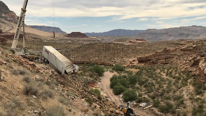 Crews use a crane to lift a trailer out of the Virgin River Gorge outside of St. George on May 9, 2018. The truck plunged into the wash May 8; the driver died.