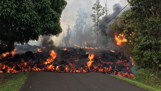 This image obtained May 9, 2018, released by the US Geological Survey shows a lava flow moving on Makamae Street in Leilani Estates at 09:32 am local time, on May 6, 2018 in Leilani Estates, Hawaii.The Kilauea Volcano, the most active in Hawaii, was highly unstable on May 6, 2018, as lava spouted into the air and fissures emitted deadly gases -- hazards that have forced thousands of people to evacuate.