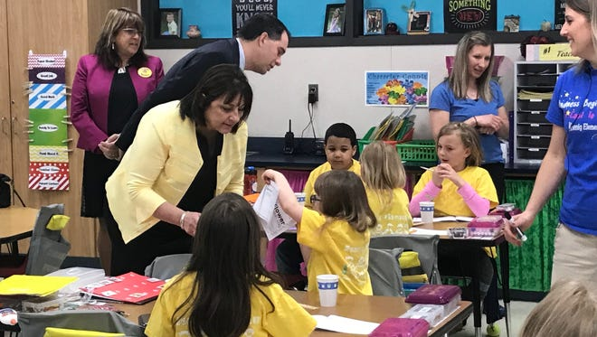 Wisconsin First Lady Tonette Walker help first-graders with a project involving plants at Koenig Elementary in Two Rivers May 18.