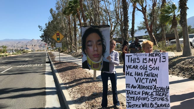 Storey Lantry Chavira stands with a sign in front of Stepping Stones Learning Center in Palm Springs with a sign alleging the center's director assaulted her 13-year-old son.