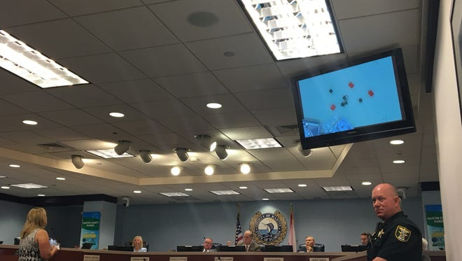 Martin County School Board member Tina McSoley on May 22 uses Monopoly money and figures to explain school funding to County Commissioners.