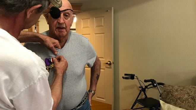 Jerry Pieschel pins the recovered medals to his stepfather Joseph Archambault's shirt during his birthday celebration Friday.