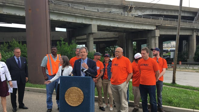 Sen. Sherrod Brown, flanked by members of the Laborers International Union, stands in front of the Western Hills Viaduct on Tuesday.