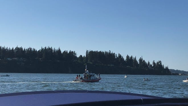 A Coast Guard boat and other vessels search the waters off Bainbridge Island for the plane that crashed there Sunday evening.