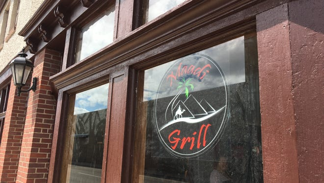 A Maadi Grill sign hanging outside the new downtown restaurant on Charles Street.