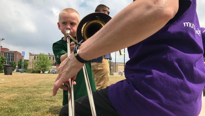A member of the Muncie Symphony Orchestra helps a young boy try his hand at playing a trombone during the orchestra's instrument petting zoo at Foodie Friday in Muncie on Friday, June 1, 2018..