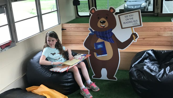 Laine Campbell, a second-grader at Discovery School, looks over a book on American history aboard Murfreesboro City Schools' new mobile library.