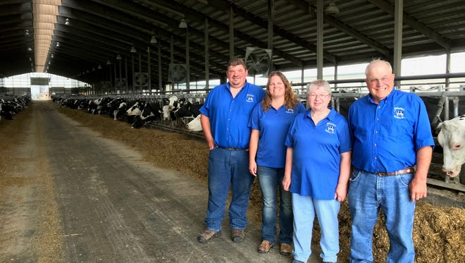 (From left) Joe, Michelle, Marilyn and Jerry Neuser pose by their cows in one of the barns on the United Visions Dairy farm.