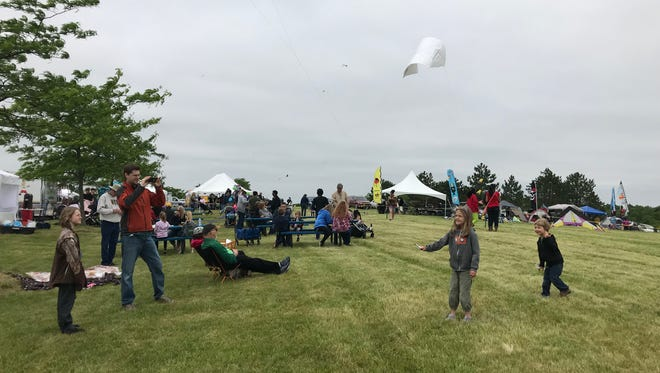 Joe West of Ypsilanti watches his children, Lewis and Clara, fly their kites.