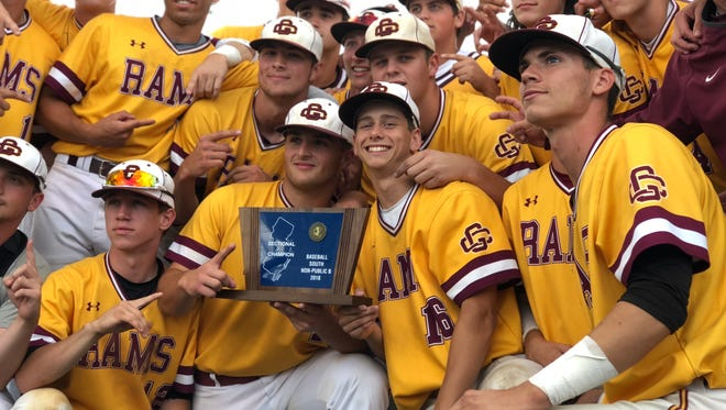 Pitcher Andrew Vail (16) helps hold up the South Jersey Non-Public B trophy.