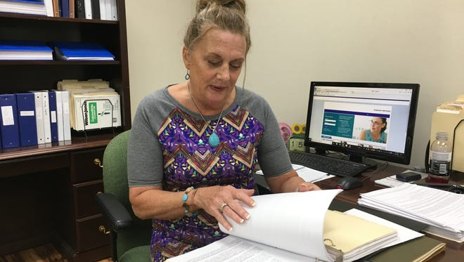 """Dover City Clerk Carla Anderson thumbs through a quick-reference guide Town Hall staff jokingly refer to as """"The Bible."""" It contains often-needed information that could be posted on a website, as well as indexes and locations where to find lesser-needed information."""