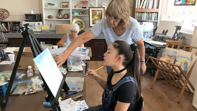 Olivia Holguin (seated) gets instruction from local artists Dorothy Palser/Waddell at the Deming Arts Center, 100 S. Gold Street.