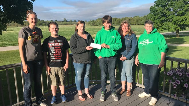 Meghan LaCrosse, club president, left; Riley Phillips, sergeant of arms; Franni Malcore, Green Bay Insurance Center Agent representing Mutual of Wausau; Jacob Fritschler, club treasurer; Sue Fritschler, adult leader; and Theresa Kinnard, general leader, pose for a check presentation photo.