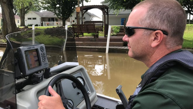 Travis Hartman, administrator for the Lake Erie fish management program, pilots a boat along the Sandusky River during a grass carp sampling in June 2018. Twenty eight adult grass carp were found last year in the Sandusky River, which runs into the mouth of Sandusky Bay before emptying into Lake Erie.