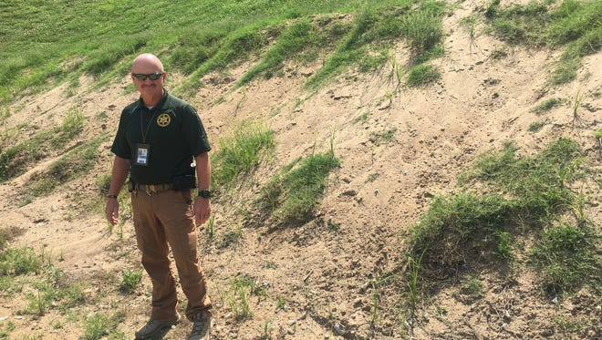 Williamson County Sheriff's Office Sgt. Denny Elliott stands in front of the berm at the WCSO gun range. Since 2015, the department has requested funding needed to remove several tons of lead from bullets shot into the berm over time. That funding has never been approved, raising questions about potential health and environmental impacts from the lead.