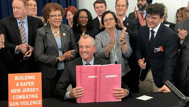 Gov. Phil Murphy holds up the six gun control measures he signed into law at a ceremony in Trenton on June 13, 2018.