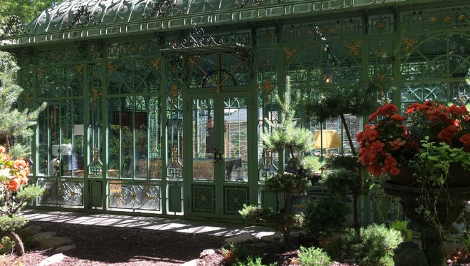 The conservatory built in the 1920s in Germany anchors the beautiful Venegas garden. The wrought iron detail and leaded glass windows are beautiful. It is surrounded by flowers.