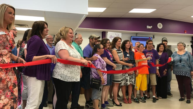 Community members join Holiday House Executive Director Deanna Genske and The Chamber of Manitowoc County Executive Director Karen Nichols in a ribbon-cutting ceremony to celebrate the Holiday House's new name and logo Wednesday.