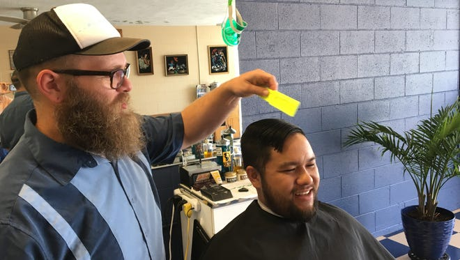 At Blue Collar Barbershop on June 14, 2018, owner Jordan Sadberry starts a fade on client Niko Ngo, who drove to the shop from Forsyth, in Taney County.