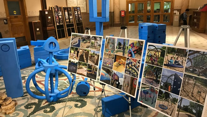 Blue blocks are used for children to design what they want on renovated playgrounds. The blocks and photos were on display during a City Hall news conference about the MKE Plays initiative.