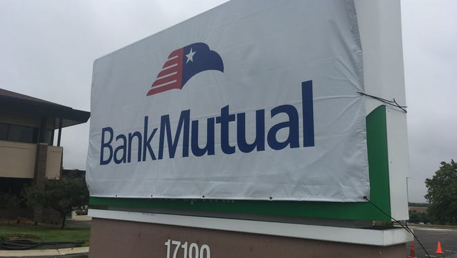 A temporary Bank Mutual sign covers a newly installed green Associated Bank sign at a Bank Mutual branch in Brookfield. The conversion of Bank Mutual to Associated is set for this weekend.