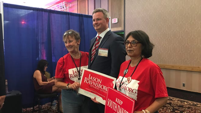 Jason Ravnsborg poses for photos with supporters Saturday in Pierre.