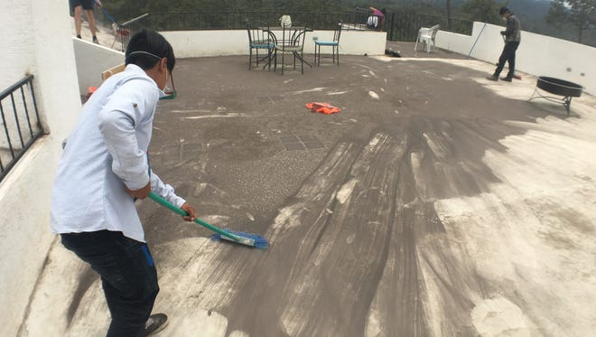 People work to clean up ash from the Fuego volcano eruption in Guatemala on June 4, 2018 at the school and clinic run by Ordinary Missionaries  in El Rosario, Guatemala.